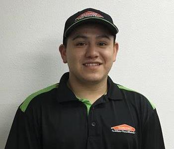 Crew a SERVPRO tech in front of a white wall dressed in a SERVPRO jersey he has brown hair and eyes he is wearing a hat.