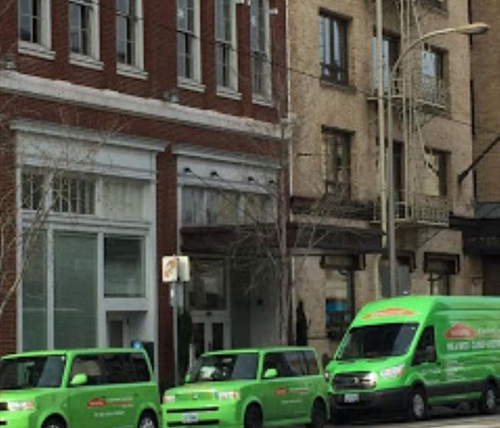 3 SERVPRO vehicles front of building